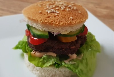 burger in a bun on a white plate