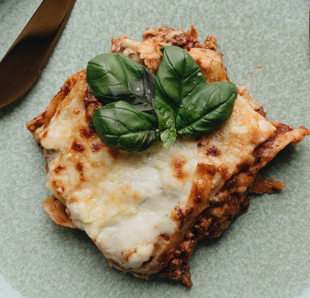 slice of lasagne on a green background