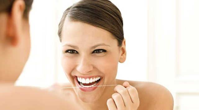 Woman flossing and keeping a balanced oral microbiota