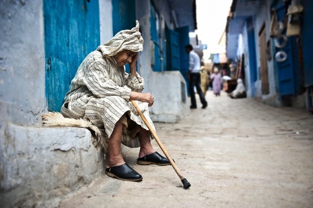 Old man looking siting in the streets of the medina of Chefchaouen