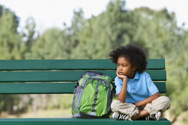 Girl (7-9) sitting on park bench