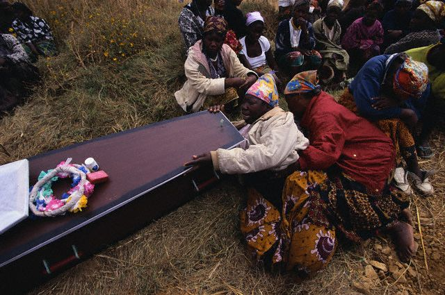 ca. 1985 - 2000, Lusaka, Zambia --- A wife mourns over the coffin of her husband who died from AIDS-related illness. --- Image by © Jeremy Horner/Corbis