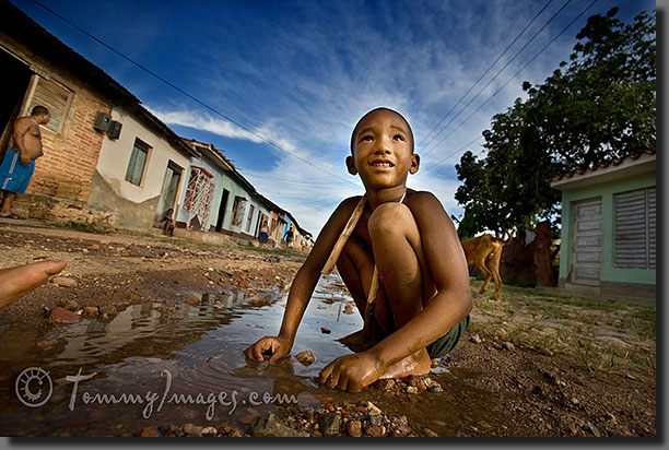 Trinidad, Cuba - A young Cuban boy plays in a puddle, on an unpaved road in the outskirts of Trinidad.