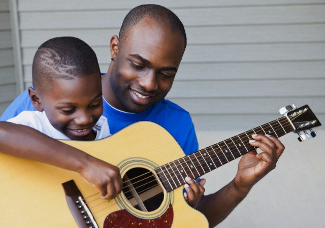 Teacher's showing boy (6-7) how to play guitar --- Image by © Greg Vote/Tetra Images/Corbis