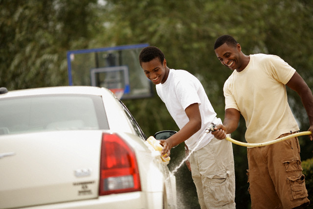 Father and Son Washing Car --- Image by © David P. Hall/Corbis