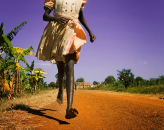 Girl (8-9) running barefoot along dirt road, low section