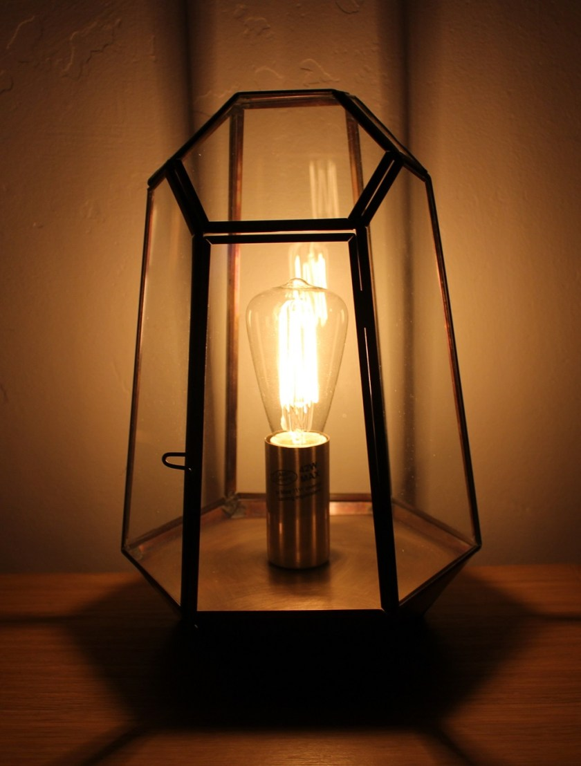 Litecraft Terrarium Candle Lantern Table Lamp - Antique Brass with edison screw filament squirrel cage light bulb. Lamp lit up in semi darkness, picture taken from the front of the lamp