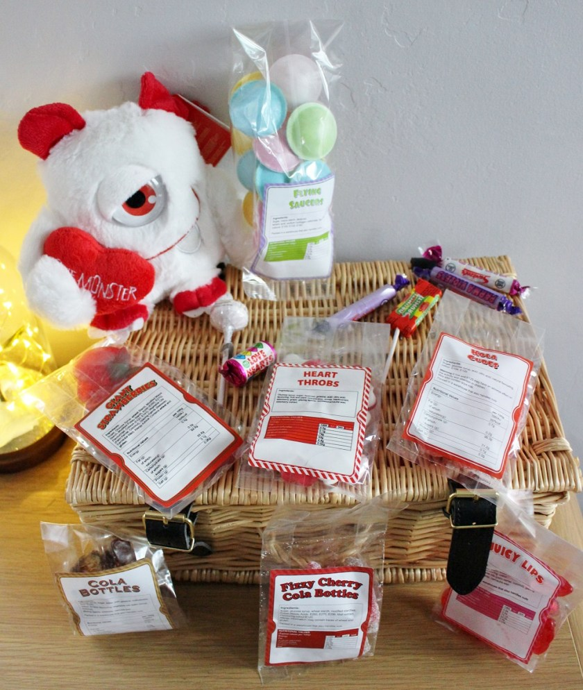 MenKind PERSONALISED SWEET HAMPER WITH CUDDLY TOY MONSTER. Monster sat on top of the hamper alongside some of the packets of sweets.