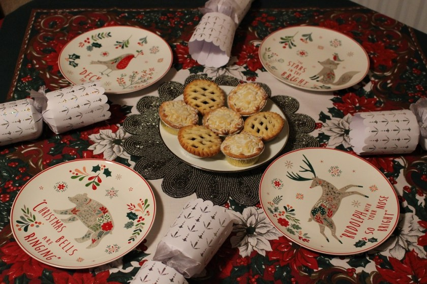 Christmas at Debenhams, selection of small multicoloured Christmas plates featuring animals; robin, bear, fox and reindeer places with crackers and mince pies