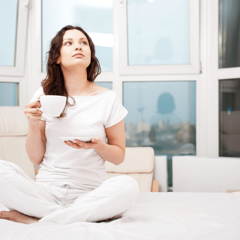 Lady relaxing on a sofa with a cup of tea.