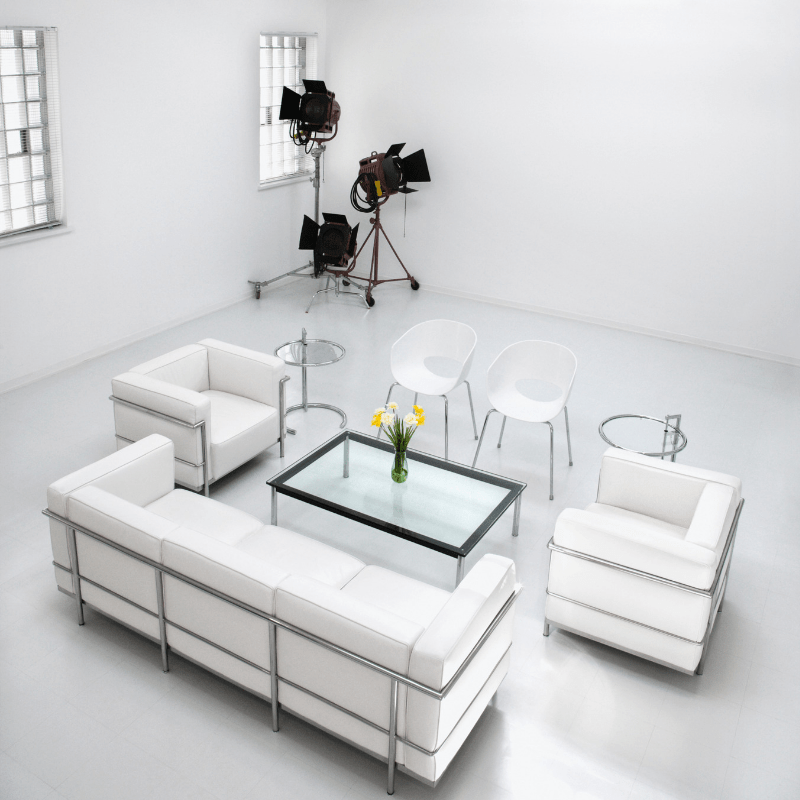 White living room including sofa, table and some flowers.