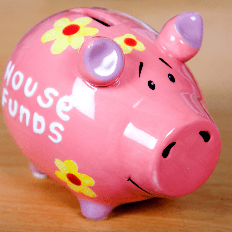 Pink piggy bank with house funds on the side