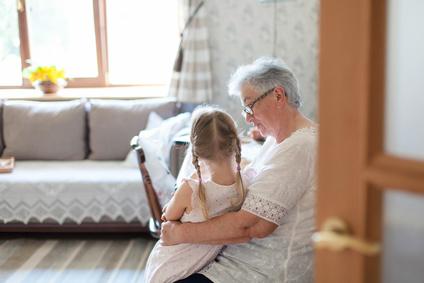 Grandmother is hugging granddaughter in cozy home living room ...