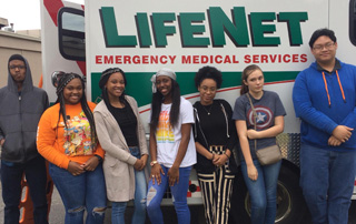 Arkansas High School students stand in front of a LifeNet ambulance.