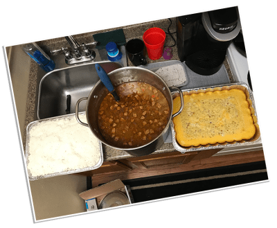 A pot of gumbo with cornbread and rice sitting on the stove in the LifeNet Air hangar. It was cooked by a family as a thank you gift for transporting their son.