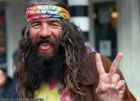 Hippie giving the peace sign - by Deanne Fitzmaurice