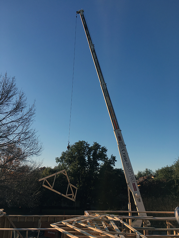 using a crane to set roof trusses
