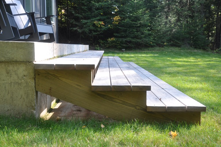 simple detail of deck steps down to the grass
