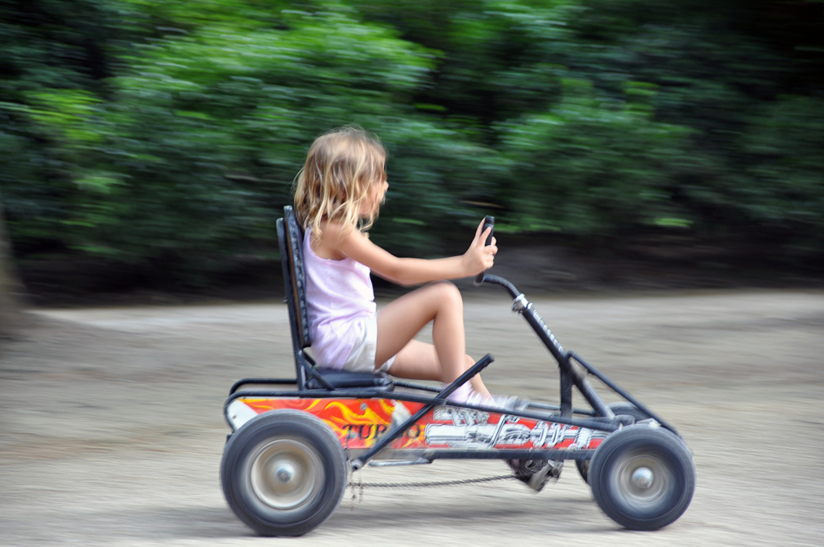 Kate Borson riding a go cart in Paris Park