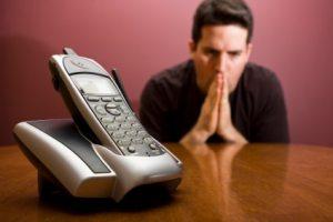 Man praying for the phone to ring