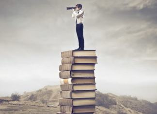 self growth; man standing on stack of books