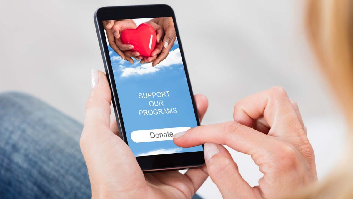 woman holding phone donating online