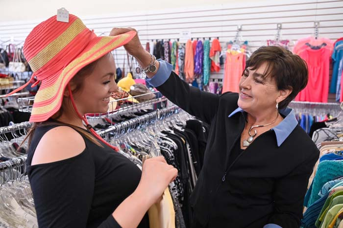 two thrift store employees having fun with a women's hat