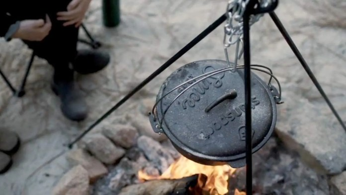 A Stansport tripod holding up a large Dutch oven simmering soup over a campfire.