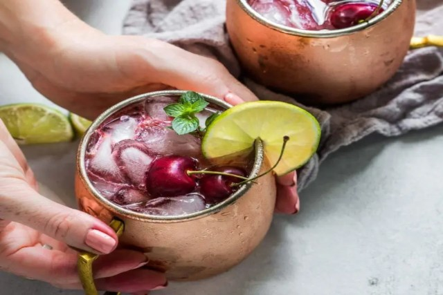 Someone was holding a copper cup filled with cherry Moscow Mzi cocktail, topped with lime, fresh cherries and mint leaves.