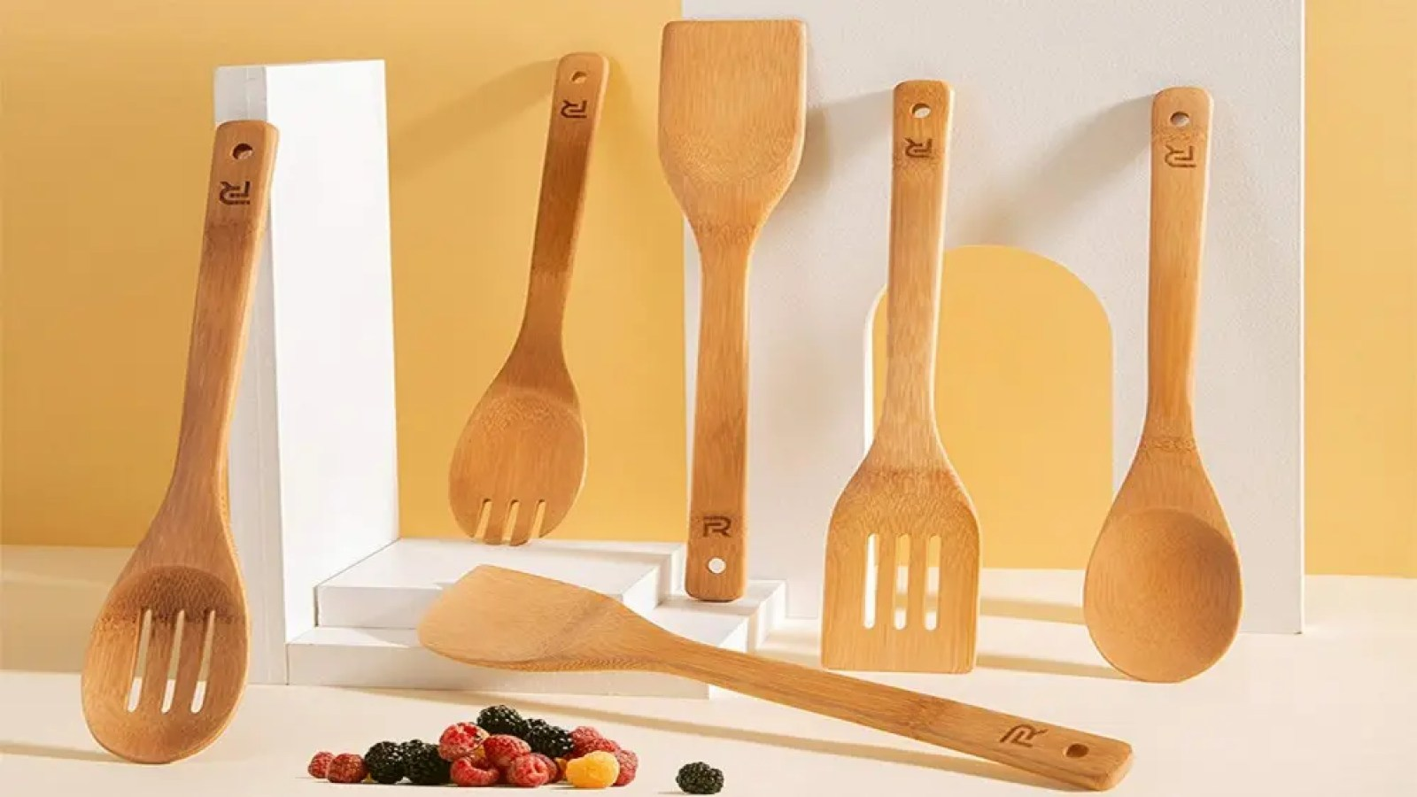 A set of 6 bamboo cooking utensils presented with fresh berries in the front.