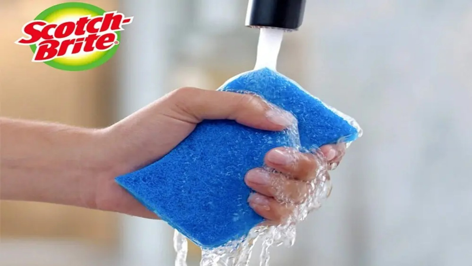 Someone holding a fresh sponge under the faucet, with the scotch-brite logo in the top left hand corner of the image.