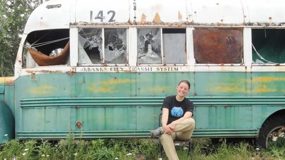 Женщина, сидящая на стуле перед зеленым, желтым и белым автобусом 142 от