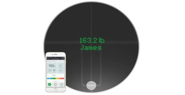 Black QardioBase2 smart scale and its supporting application on the phone.