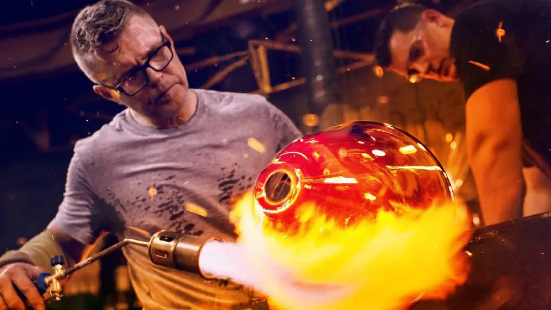 A glassblower on the show 'Blown Away' sculpting molten glass.