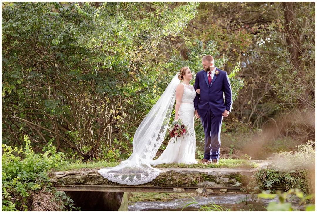 bride with long veil and groom on bridge