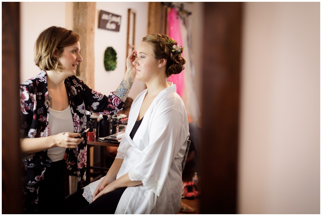 getting ready shot bride in white robe with makeup