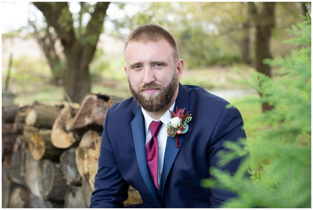 groom portrait outdoors with logs