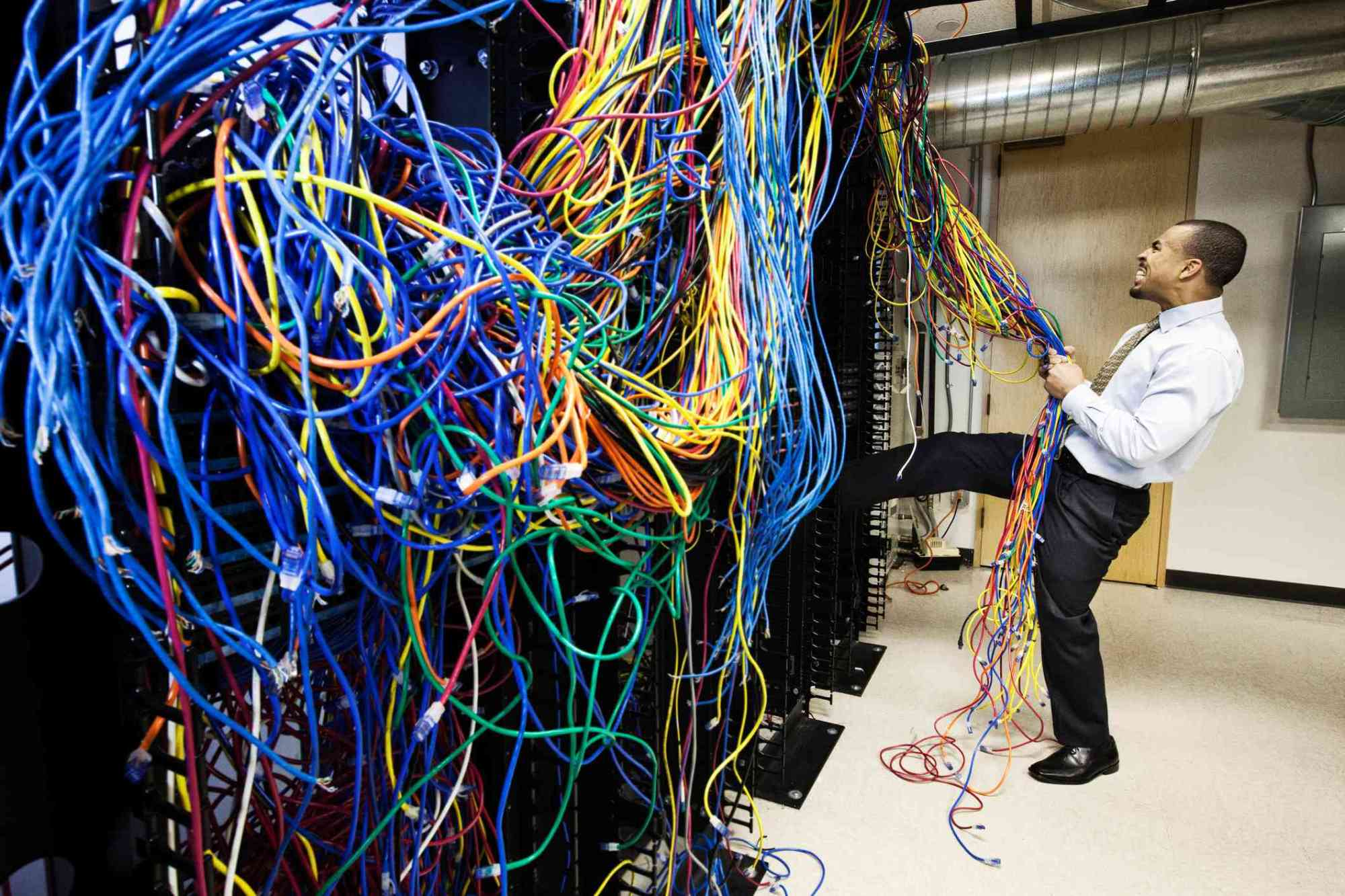 hight resolution of a technician pulling on a tangled mess of cat 5 cables in a computer server room