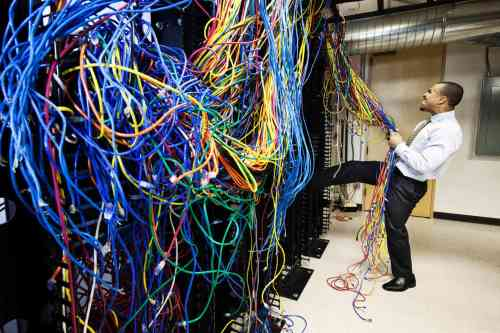 small resolution of a technician pulling on a tangled mess of cat 5 cables in a computer server room