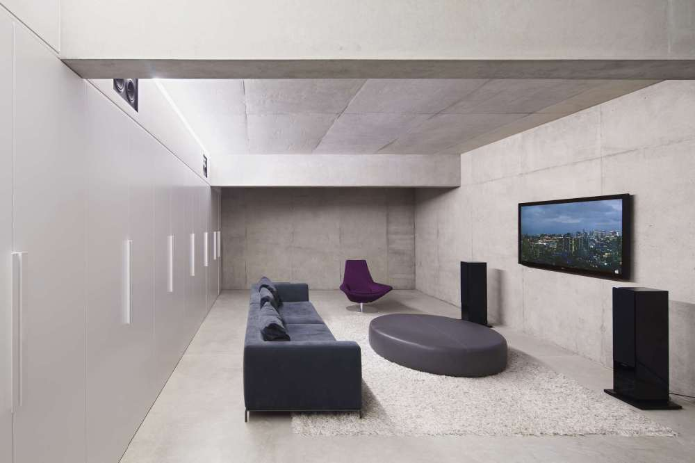 medium resolution of a modern living room with wall mounted tv stereo speakers and a couch