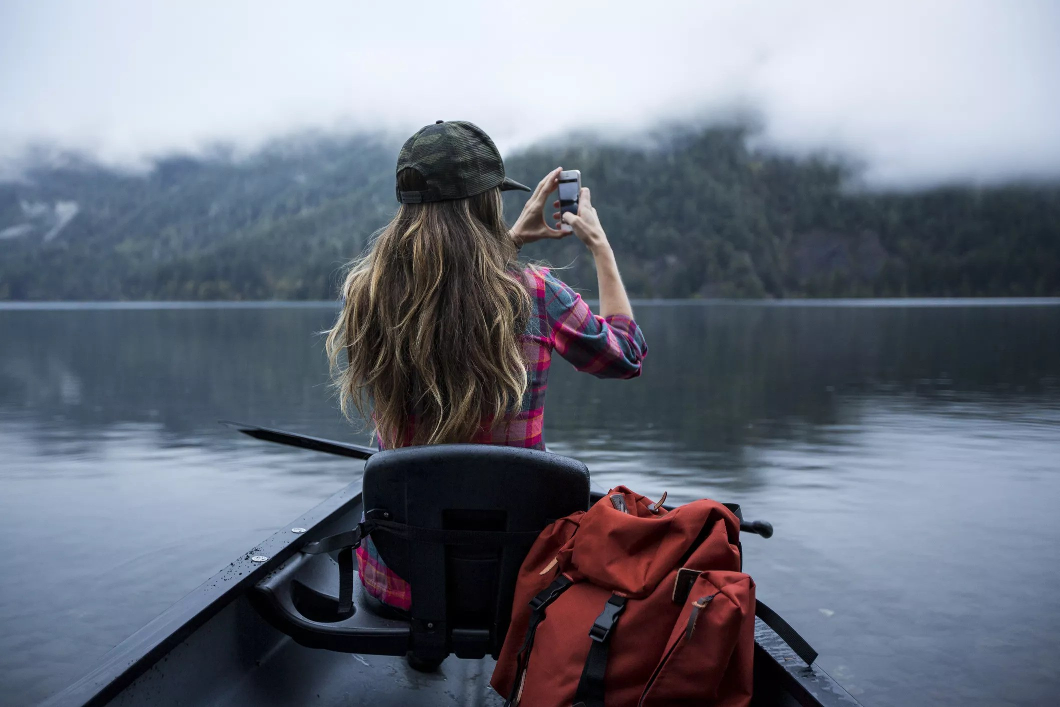 An image of a woman on a boat taking a photo of the surrounding water and landscape with her smartphone.