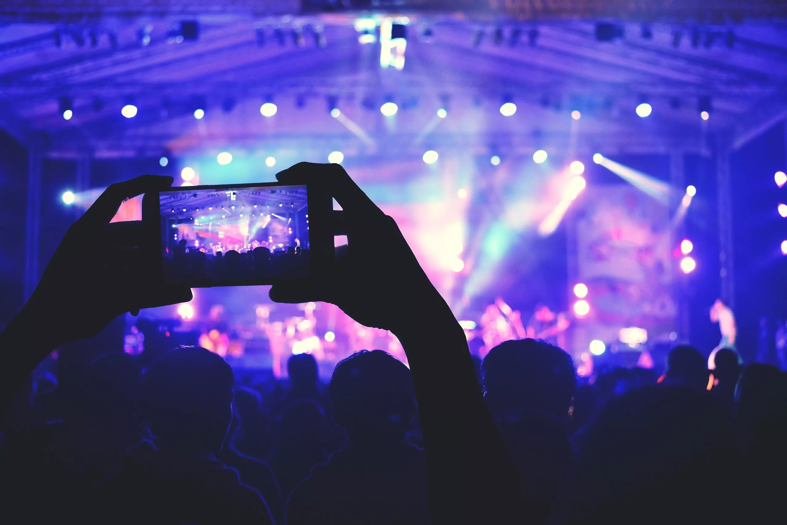 An image of someone taking a photo of a concert with their smartphone.