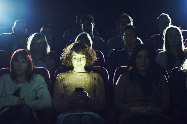 Person using their phone in a movie theatre during a movie