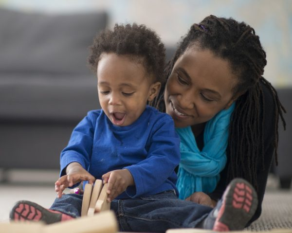 Woman lying on floor next to toddler boy playing with wooden blocks