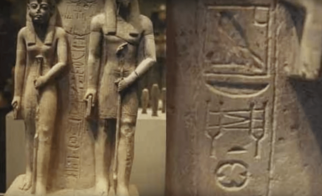 A depiction of tuning forks is seen on a statue of Isis and Anubis, each holding a rod. Between the deities, a carving shows two tuning forks that seem to be connected by wires. Beneath the forks, a rounded object with four prongs is centered, and it almost appears like an arrow points upward.