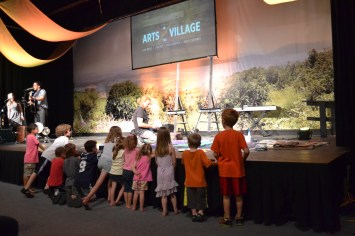 William Butler paints his canvas as many children look on and admire his work.