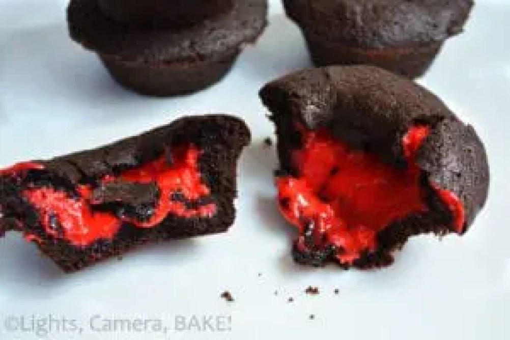 Bleeding Buttercake Stuffed Chocolate Cookie Cups. Oooey gooey vanilla buttercake filling coloured red, encased in a soft and chewy chocolate cookie. These are perfect for a Halloween treat or any other special occasion. #recipe #cookiecups #buttercake