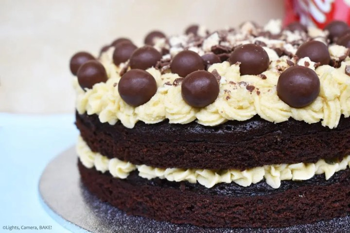 Side of a two tiered Malteser Chocolate Cake with malted buttercream middle and top with crushed Maltesers and full Maltesers