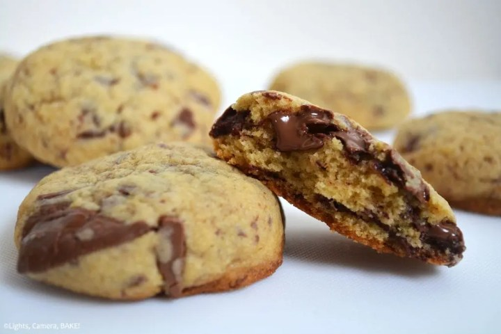 REAL Chocolate Chocolate Chunk Cookies. Half a cookie with melty chocolate leaning on another chocolate chunk cookie with more cookies in the background