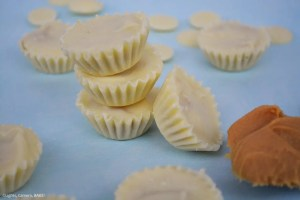 White Chocolate Peanut Butter Cups are mini cups with a white chocolate casing and a sweet and creamy peanut butter filling with a scoop of peanut butter beside them.